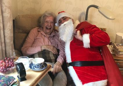 Hungerford Care Home, Berkshire. Father Christmas (Care Assistant Tiago Casthaneira) visiting resident Alberta Taplin on Christmas morning