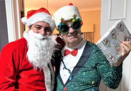 Hungerford Care Home, Berkshire. Father Christmas (Care Assistant Tiago Casthaneira) with resident Nigel Jenks on Christmas morning
