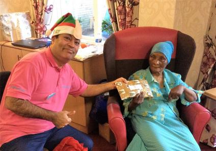 Uplands Care Home, Streatham. Magic Moments Club Coordinator Muhammad Ali presenting resident Adijat with a Christmas gift