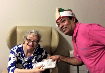 Uplands Care Home, Streatham. Our Christmas Elf (Magic Moments Club Coordinator Muhammad Ali) giving resident Linda an early Christmas present