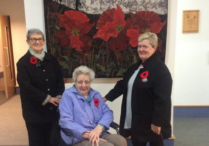 Team member Irene Monaghan, resident Margaret Ingram and team member Frances McFayden beside the quilted poppy picture at Erskine