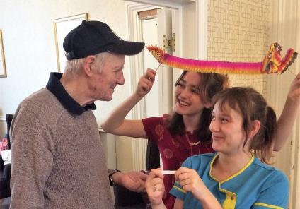 Carlton Mansions Care Home, Bristol. Magic Moments Club Coordinator Ella and Carer Annie present resident Terry with his fortune cookie 'The colour blue will be lucky for you'