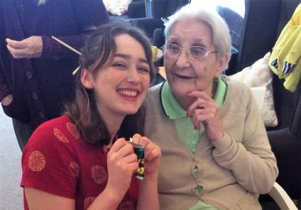 Carlton Mansions Care Home, Bristol. Magic Moments Club Coordinator Ella and resident Muriel about to open their fortune cookies