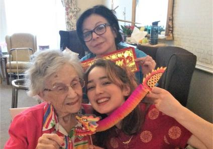Carlton Mansions Care Home, Bristol. Resident Judie, Magic Moments Club Coordinator Ella and Carer Louisa painting a traditional picture of the zodiac pig with water colours