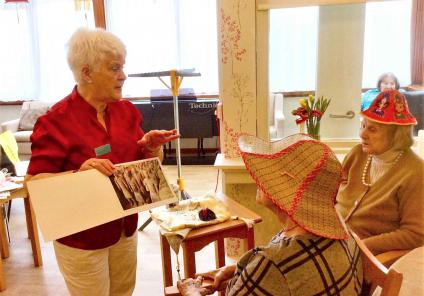 Buchanan Lodge Care Home, Glasgow. Our Activities Volunteer, Flora gave a fascinating presentation about her trip to China. Residents Joan and Rita try on the Chinese headwear whilst looking at Flora's photographs