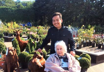 Resident Betty and Care Assistant Kumar admire the wooden sculptures!