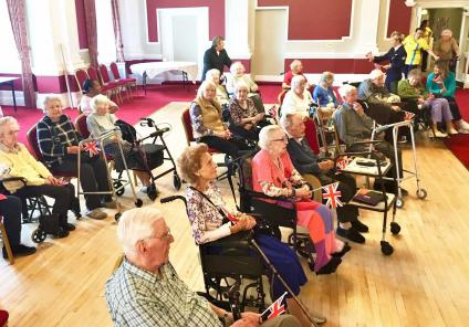 Residents and their relatives gather in the Crystal Ballroom for a performance from The Bluebirds