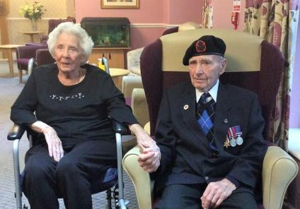 Eric proudly wears his medals with wife June