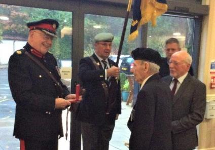 Eric receiving his medal from Major Stanley Hardy