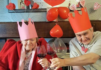 Kingston Care Home, Surrey. Residents Mary and Duncan raise a glass to romance as they are crowned 'Mr & Mrs Valentine'!