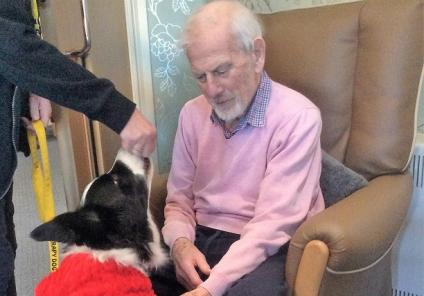 Resident David with Jack our therapy dog who sported his own festive costume