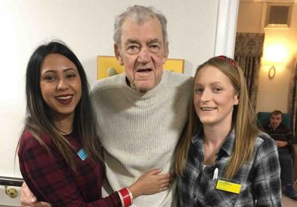 Hungerford resident Kenneth wearing his tartan with Magic Moments Club Co-ordinators Kanika and Sarah