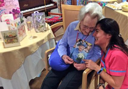 Peggy opening her card from The Queen with Magic Moments Club Coordinator Mia