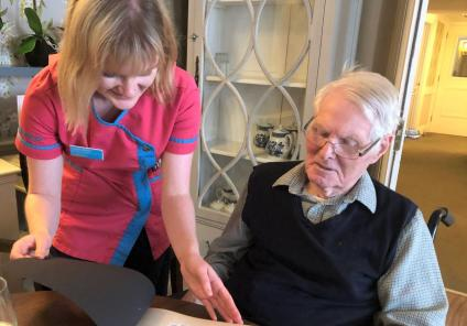 Mill House Care Home, Oxfordshire-Magic Moments Club Coordinator Lauren and resident Anthony looking through the book together