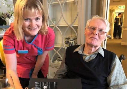 Mill House Care Home, Oxfordshire-Magic Moments Club Coordinator Lauren presenting the book about his great uncle to resident Anthony