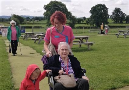 Ross Court Care Home, Herefordshire-Little Archie helps Magic Moments Club Coordinator Clare push resident Barbara along