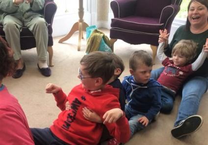 Ross Court Care Home, Herefordshire-Resident Pam claps as the children and childminder Jo perform the Rowing Boat Song for us