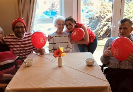 Scarborough Hall Care Home, North Yorkshire. Resident Ann, team member Andrew, resident Jessie, team member Leanne and resident Dennis with their Red Nose Day balloons