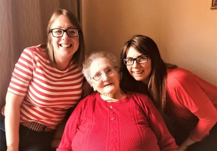 Scarborough Hall Care Home, North Yorkshire. Team member Charlotte, Resident Elsie and team member Charrdi all dressed in red