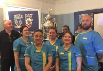St Oswalds House Care Home, Cheshire-Team members in front of Warrington Wolves' Challenge Cup trophy
