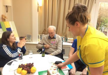 Senior Carer Zoe White presents Frantz with his Birthday cake