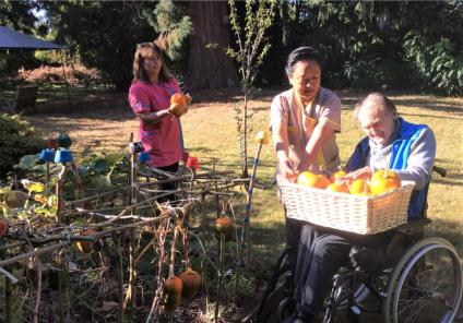 The Berkshire Care Home, Wokingham-The basket is getting fuller and fuller! Resident Donald and team members Julia and Dhan harvesting our vegetable patch