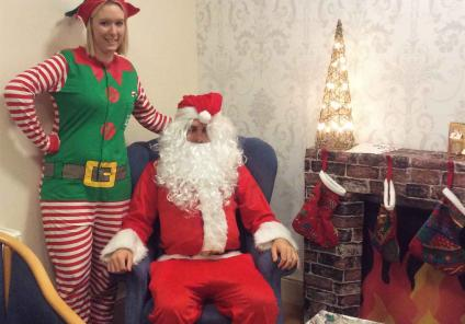 Father Christmas and his Elf helper by the fireplace- Magic Moments Club Co-ordinators Sam and Alison