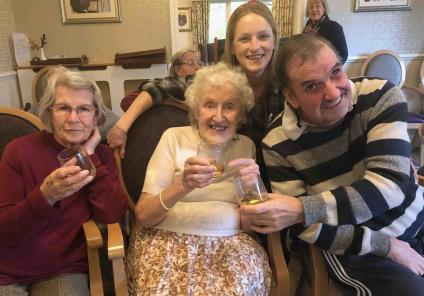 Hungerford Care Home residents Elizabeth, Audrey and Nigel enjoy a wee dram with Magic Moments Club Co-ordinator Sarah